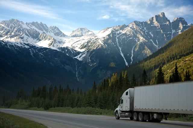 Bílý nákladní automobil jede po cestě mezi horami a přírodou, kolem zasněžených vrcholků hor.