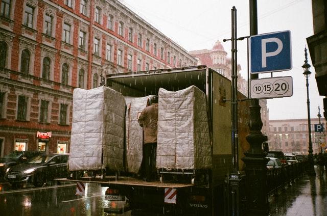 Město, historické budovy a nákladní automobil, jak vykládají náklad pod plachtami, když prší.